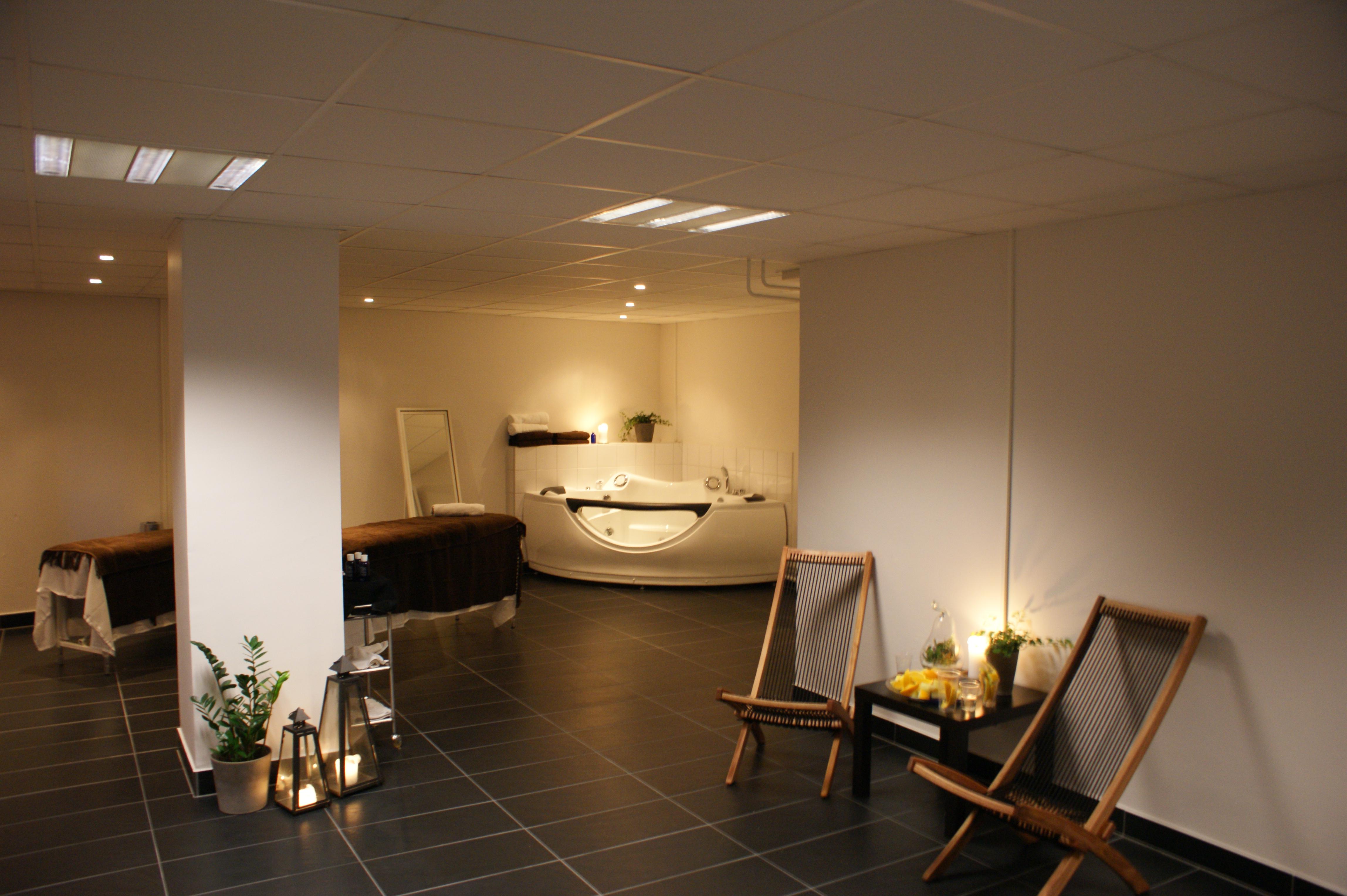 Ett spa Malmö med jacuzzi, bord, stolar och massagebritsar.